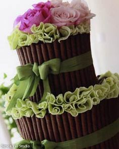 Green and pink wedding cake wrapped with olive green satin ribbon. The cake is decorated with cylindrical tubes of chocolate, green ruffled fondant and pink and fuchsia roses wedding cake topper.