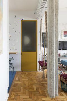 Cozinha recebeu papel de parede estampado, porta amarela e piso azul.