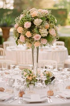 For a garden wedding it doesn't get dreamier than centerpieces of peach and pink roses surrounded by greenery.