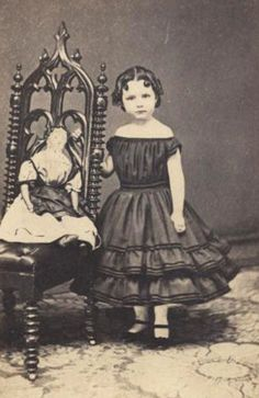 A stately china head lady doll sits beside her owner, a young lady from the 1860's.
