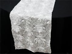 Paradise Rosette Table Runners - White | This parcel from paradise will drift you enchantingly to the empyreal fantasy world of a divine paradise. This mesmeric runner comprises of comely satin roses that pop-out to give an amazingly elegant 3-D effect that is attributed to paradise. The magical glistening flowers are so enticing that will make everyone's jaw drop with fascination. The embossed rose pattern will add flair and character to any drab piece of furniture or dreary decoration…