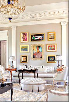 Love the gold framed colorful art in the elegant beige room