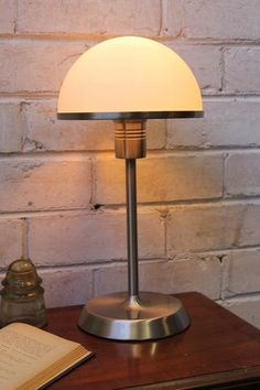 This Art Deco style table lamp will add some glamour and timeless appeal to your bedroom or lounge. Featuring a 3 stage dimming touch base for ease of use, it comes in a brushed chrome finish. Art Deco Table Lamps, Metal Table Lamps, Bedside Table Lamps, Lamp Bases, Lampshade Designs, Dim Lighting, Hand Blown Glass, Glass Shades, Chrome