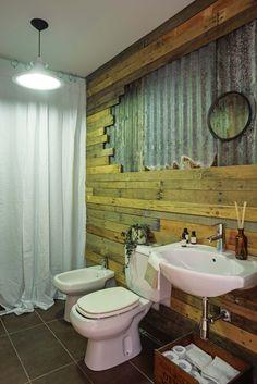 Baño con revestimiento de chapa acanalada y madera que aportan un toque industrial.