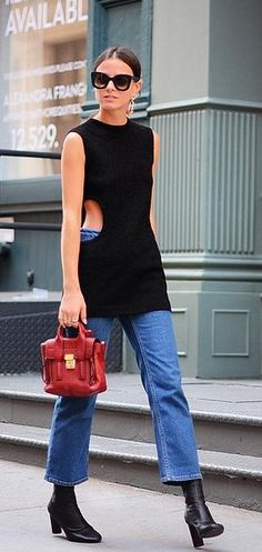 A sweater vest, cropped jeans, and black ankle boots.