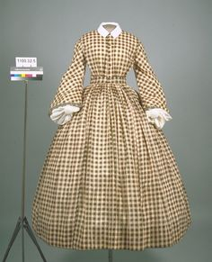 USA, 1853-1857, wool dress  Dress; green, tan, and cream wool plaid, with bell sleeves. Rounded neckline with center front closure of ten hooks and eyes. Nine green thread covered buttons accent front closure. Bell sleeves with trim at cuff. Banded waist. Gathered full length skirt. Hem of skirt is bound with green tape. Bodice and sleeves are lined.