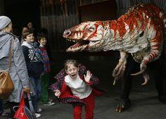 Children react as a carnivorous theropod Australovenator dinosaur walks thru crowds along the Southbank, in England. Erth's Dinosaur petting zoo from Australia