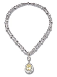 A BELLE EPOQUE DIAMOND PENDENT NECKLACE   Suspending a yellow pear-shaped diamond within a diamond surround to the twin graduated diamond collet and link neckchain, circa 1910, 38.0 cm. long