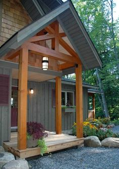 landscaping with crushed rock, boulders and perennials. Like the grey board and batton siding with the cedar shakes