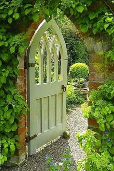 Garden gate idea inspiration: a gothic wood door to a beautiful lush green garden beyond climbing vines on a stone wall. #gardenideas #gardengate #secretgarden #romanticgarden #frenchcountry