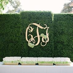 Escort card display, hedge backdrop, planted in flower boxes. Green and white. Gold Monogram. Planning & Design:   riley loves lulu weddings Photograph by pictiliom floral by main street flora gardens