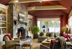 deco-campagne-chic-avec-un-cachet-rustique-couleur-peinture-mur-rouge-cheminée-rustique-bibliotheque-canapé-et-fauteuil-beige-accennts-deco-rouges