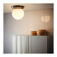 The glass shade provides balanced general lighting throughout the room.