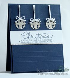 handmade Christmas card from Kreative Kristie ... clean and simple design .... navy blue with white and sparkly silver ... raised background panel with embossed lines ... adorable jingle bells die cut from silver glimmer paper and hung with white cord in a bow ... wonderful card!