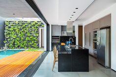 Linhas retas e grandes vãos integram casa contemporânea