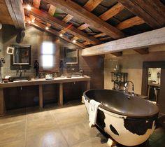 Cuarto de baño con techos abuhardillados, nevera con exterior simulando piel de vaca y muebles para lavabo en madera de tonos rojizos