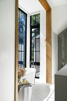 A standing tub is placed in front of tall windows, which can be covered with blinds. Save for a finished basement and a few walls above ground, this Ontario, Canada residence, designed by Nicholas Ancerl of Ancerl Studio, was built completely anew to fulfill the homeowner's wishes of a country-chic home. #interiordesign #architecture #homedecor Black Window Frames, Black Windows, Tall Windows, Ontario, Home Office, Spa Like Bathroom, Bathroom Bath, Bath Tub, Modern Bathroom