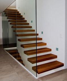 Escalier marche en porte à faux avec garde-corps en verre.
