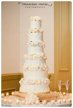 Very tall white buttercream wedding cake with fresh flowers are separated by each layer. Wedding cake delivered to Palma Ceia Country Club in South Tampa Florida.