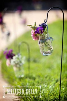 These mason jar flower vases hanging on shepherd's hooks lined the sidewalk (a.k.a. aisle) at my sister's outdoor wedding. Photography by http://melissakellyimagery.com/