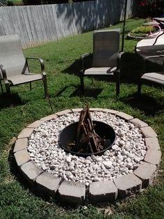Redo of our firepit. Old metal barrel cut in half.leftover landscape bricks and only purchase was riverrock