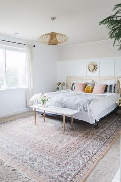 Wainscoting covers a dingy beige wall and a giant rug covers dingy beige carpet -- how to make a beautiful bedroom in a rental
