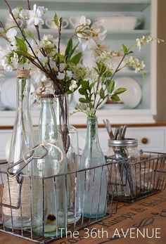 Vintage bottles filled with flowers grouped in metal basket - love!