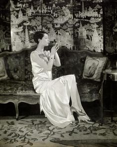 Vogue ~ Charles Sheeler ~ August Portrait of Ilka Chase wearing a satin dress by Chanel, and a long pearl necklace, sitting in front of a Chinoiserie screen. Chanel Canvas, Chanel Art, Rodgers And Hammerstein's Cinderella, York Hotels, Sparks Joy, Long Pearl Necklaces, Cecil Beaton, Old Hollywood Glamour, Vintage Chanel