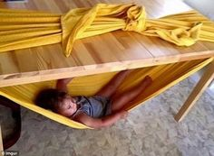 One parent used a large piece of fabric to make a hammock under the table for their child to lie in