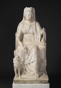 An ancient Roman marble statue of a seated Cybele with the portrait head of her priestess, c.AD 50; she is depicted with the goddess's symbolic attributes, including a mural crown (symbol of her role as protectress of cities); wheat and poppy heads (as an agricultural goddess), a lion (symbolising her power over wild animals) and a rudder (symbol of fortune/fate) and a cornucopia (plenty). (Getty Museum)