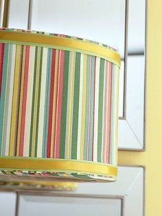 Dress up a shade with the help of fabric. Simply measure the height and diameter of the shade. Then cut your fabric accordingly, leaving about 2 inches on either side to fold and wrap inside the shade. Use spray adhesive to attach the fabric to the shade. To finish the look, add a border of ribbon around the edges./