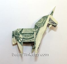 """Dollar Origami - Unicorn  via Etsy by BeanyTink""  This item is made from a single U.S. dollar.  It costs $10.  Yep.  For some folding.  At least shipping this item, which weighs less than an ounce, is only $3.50.  So $13.50 total for a folded up $1 bill, which I guarantee most of us could figure out how to fold if we sat there long enough.  And then look out, she'll have some competition!"