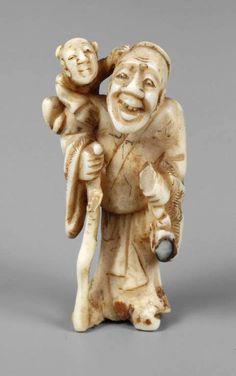 Netsuke Japan, Ende 19. Jh., Elfenbein geschnitzt, fein graviert und teils geschwärzt, stehender Alter mit Stock, einen Knaben geschultert, kleine Fehlstelle, Altersspuren, H 5 cm.