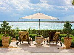 The turquoise waters of the Atlantic Ocean are just steps away from this Mediterranean stone patio. #umbrella #view #summer