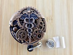 Medical caduceus steampunk badge holder features a unique watch movement design embellished with vintage color clock gears. Its a statement piece with an impressive presence. C o l o r : http://etsy.me/2mUztVn O w l : http://etsy.me/2ciJQkY H e a r t : http://etsy.me/2c7EjMY S