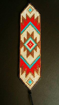 Bright and bold beaded loom bracelet handmade to order. Inspired by Native American designs with a modern edge. Using 24ct gold Japanese beads, surrounded by bright turquoise, red and pearlescent design. Edged with black cord and finished with a sliding knot and two red tassels.