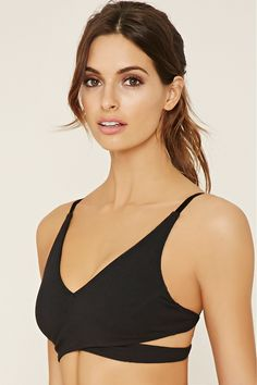 Crafted from a stretch knit, this low impact sports bra features a caged back, adjustable cami straps, removable cups, and a crisscross front.