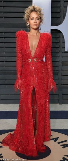 Whatever the feather: Rita Ora, 27, wore a plunging red gown which had a seriously sexy thigh-split