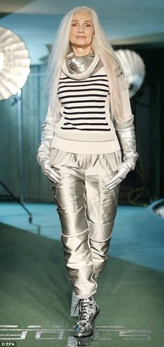 Another grey-haired beauty in a striped sweater wears silver space-suit trousers and gloves