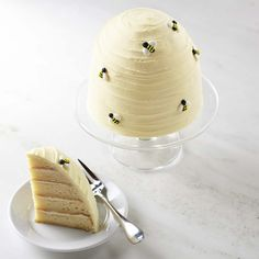 Beehive Cake - We Take the Cake, a boutique bakery in Florida, handcrafts tender almond cake and layers it with honey and almond cream cheese frosting. The creation is then cloaked in pale yellow buttercream and topped with royal icing bees.