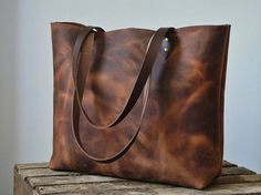 Eye-catching, rustic leather tote bag. Generous size and robust enough for daily use. Limited supply of this wonderful rugged, oiled Spanish pull-up leather: deep brown with amber undertones. Tough and durable; you can see the original texture and marks/scars in the animals skin. When stretched or scratched the colour lightens. If you rub it (or heat it gently) the marks fade. Unlined, natural suede interior. Sturdy brown shoulder straps. Internal canvas zipper pocket for phone/val...