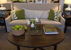 Green Home - Tan & green living room design. Linen upholstered sofa with rustic round coffee table! green throw pillows and metal lamps! green brown cream gray living room colors.