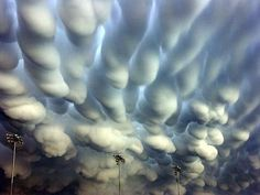 """These """"mammatus clouds"""" were photographed above Hastings, Nebraska, after a destructive thunderstorm in May 2005. Although their formation is not completely understood, these rare clouds usually develop at the base of a thunderstorm, and appear lumpy because of instabilities and temperature differences between sinking and rising air."""