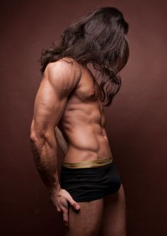 Hunky buffed male with long think brown hair and wearing a black trunk brief