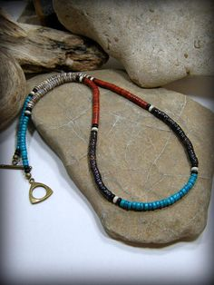 Beaded heishi necklace in stabilized turquoise, olive shell, red howlite beads and dark pen shell ... each section separated by a white rondelle seed bead, and that surrounded on each side by black rondelle seed beads. Beautiful color combination together...unusual and unique necklace that can be worn by men or women. Finished off with a brass toggle clasp. Length: You will choose the length you need from the drop down menu (the necklace pictured is 20 long). ***This will be a custom order…