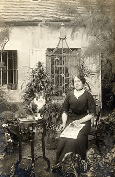 Turn of the century. Cat with bird aviary in the background. Love the garden! .... and I want the table that the cat is sitting on!