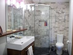 Image of Wooden Bathroom Sink Cabinet Under Large Frameless Wall Mirror and Wood Mounted Shelves with Porcelain Toilet Corner Shower Glass Panels with Stainless Steel Bar Handle Large Frameless Wall Mirror and Wood Mounted Shelves