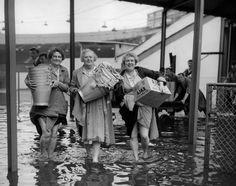 1957: Laden with pails and cloths, three members of the catering staff paddle through the flooded Wimbledon Stadium. Because of the floods, the greyhound race meeting had to be postponed. Wimbledon was one of the London areas affected by the floods caused by heavy rains.