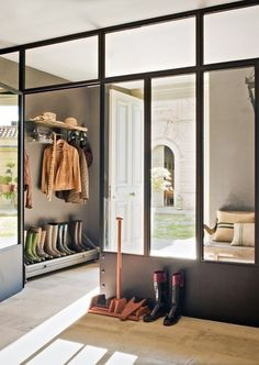 Glass panels keep this mudroom separate, while still making it feel open and bright. Great boot storage too.
