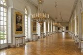 The Grand Apartment - The Cotelle Gallery - This gallery, which was cleverly built to shelter the Trianon's flowerbeds from the rigours of winter, has 11 French doors on the south side and just five on the north. It features 24 paintings (including 21 by Jean Cotelle) depicting the copses at Versailles and the Trianon as they appeared when they were created in 1687. These works are a precious record of what the gardens looked like in the seventeenth century. Sofas originally stood in the…